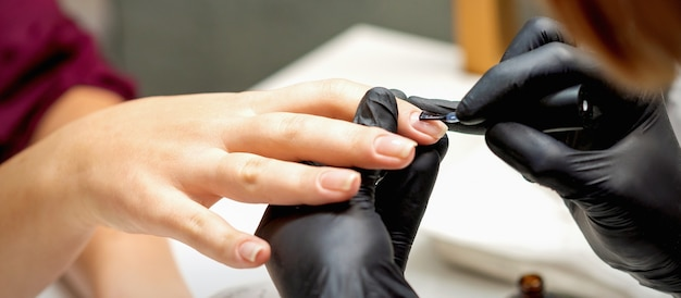 Close do mestre de manicure cobrindo as unhas com o esmalte transparente de unhas femininas em um salão de beleza