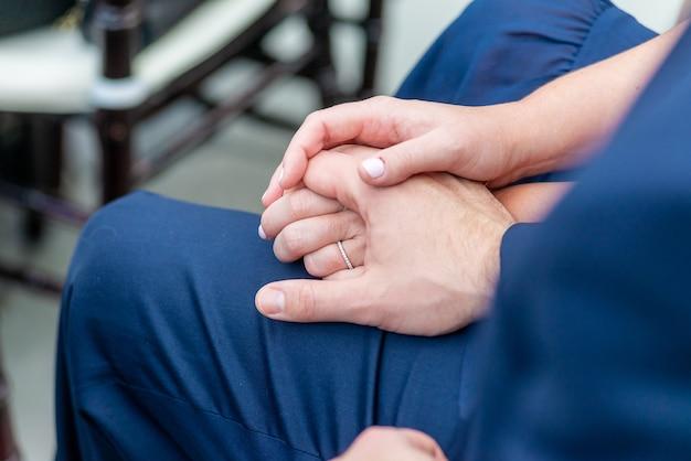 Close do noivo e da noiva sentados, com as mãos uma sobre a outra