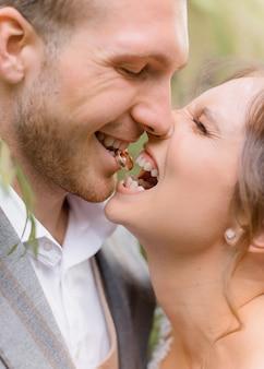 Close do noivo segurando um anel nos dentes e a noiva rindo