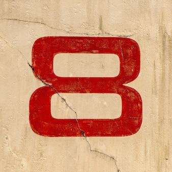 Close do número 8 pintado em uma parede de vermelho