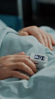Close do oxímetro no paciente na cama da enfermaria do hospital