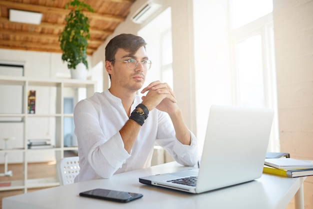 Close do pensativo jovem empresário atraente usando camisa branca no escritório