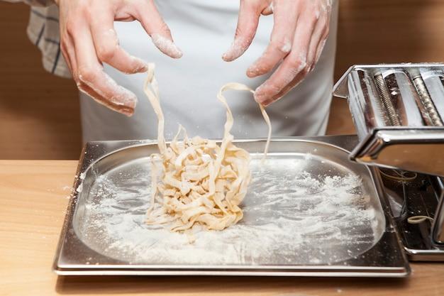 Close do processo de fazer macarrão caseiro fresco.