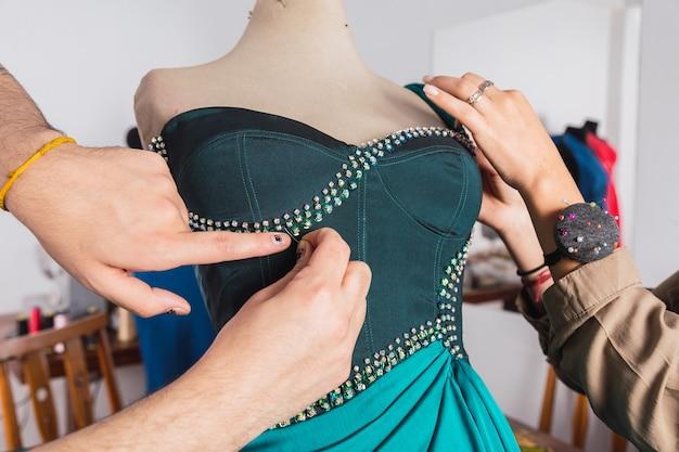 Close do processo de trabalho de alguns estilistas em seu estúdio - processo de um vestido de festa costurado à mão.