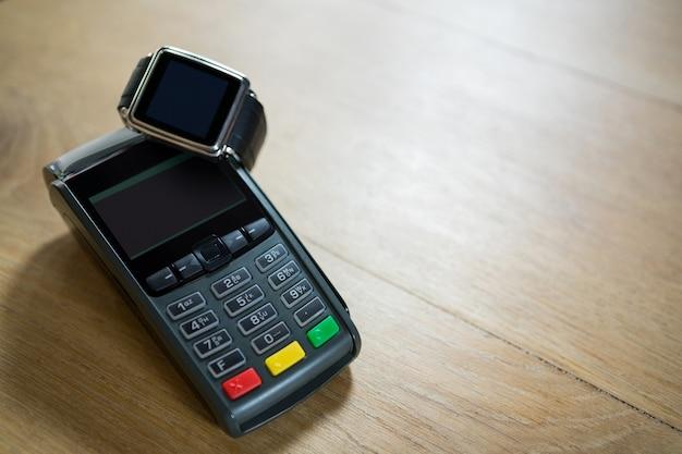 Close do relógio inteligente e do leitor de cartão de crédito na mesa de um café