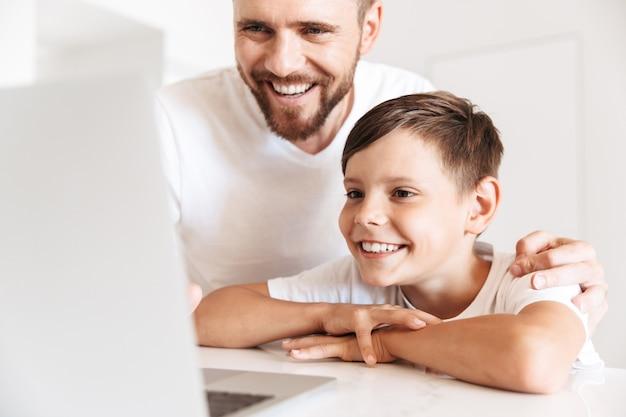 Close do retrato de pai e filho felizes, sorrindo, enquanto olha para o laptop prateado em um apartamento branco brilhante
