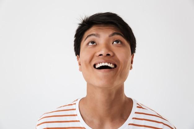 Close do retrato de um homem chinês satisfeito vestindo uma camiseta listrada, sorrindo com dentes perfeitos e olhando para cima, isolado. conceito de emoções