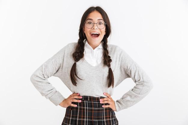 Close do retrato de uma adolescente alegre usando óculos e uniforme escolar, pensando enquanto olha para a câmera, isolada sobre a parede branca