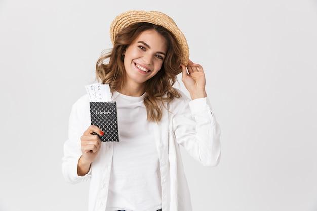 Close do retrato de uma mulher alegre em roupas casuais, segurando o passaporte e as passagens em pé, isolado