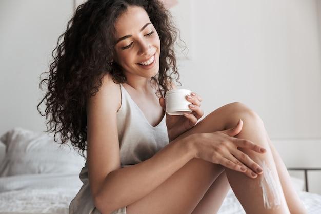 Close do retrato de uma mulher bonita com cabelo longo encaracolado, sentada na cama com lençóis brancos limpos no apartamento e aplicando creme corporal nas pernas