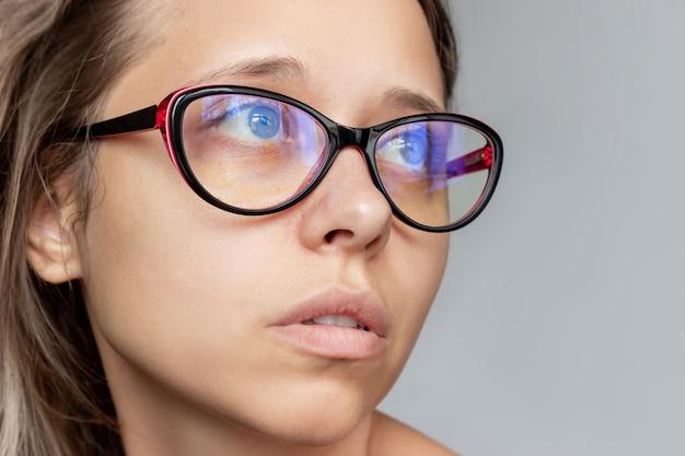 Close do rosto da mulher óculos femininos para trabalhar em um computador com lentes de filtro azuis