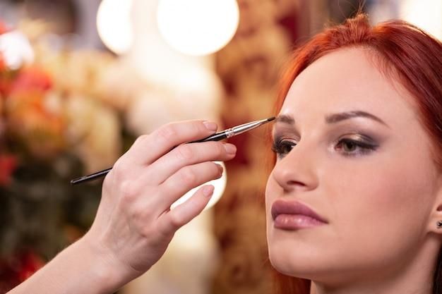 Close do rosto de mulher jovem e bonita com maquiagem de beleza