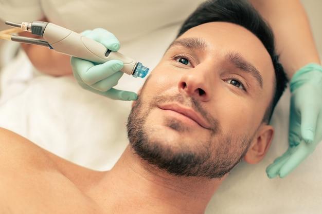 Close do rosto de um homem barbudo sorridente submetido a um procedimento agradável de nutrição da pele