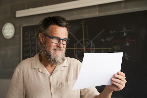 Close do rosto de um professor universitário sorridente, segurando alguns documentos, um exame, um papel