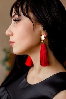 Close do rosto de uma jovem mulher com maquiagem elegante, cabelo preto e brincos vermelhos.