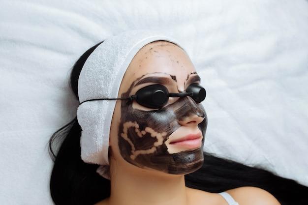 Close do rosto de uma linda garota com uma casca de carbono aplicada na qual um coração é pintado, conceito de ...