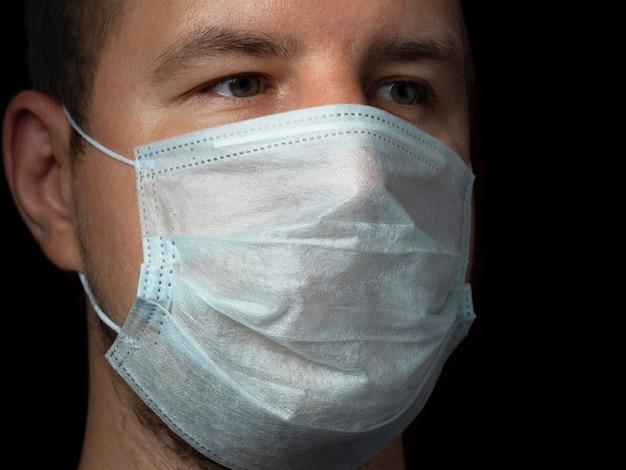 Close do rosto do homem usando uma máscara médica protetora em um fundo escuro. conceito de proteção contra o vírus covid-19 e outras doenças transmitidas pelo ar