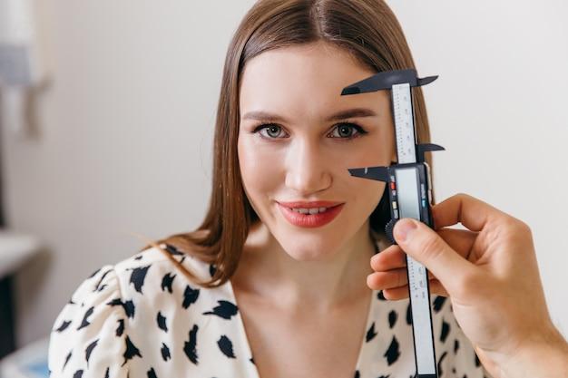 Close do rosto feminino sendo medido pelo médico de cirurgia plástica