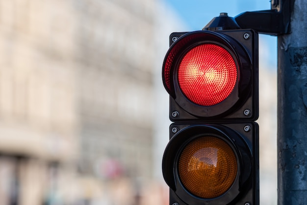 Close do semáforo de trânsito com luz vermelha no fundo desfocado da rua da cidade com espaço de cópia
