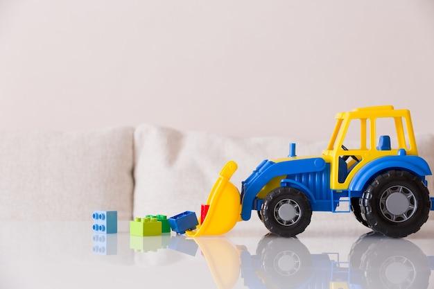 Close do trator de brinquedo infantil com tijolos de plástico coloridos ou detalhes em fundo branco
