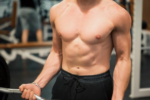 Close do tronco de um poderoso instrutor de fitness na academia
