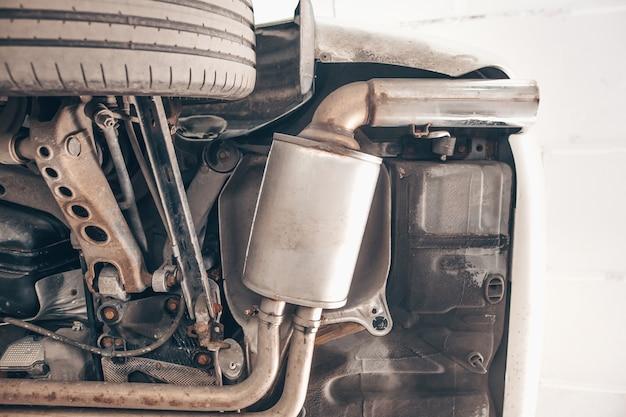 Close do tubo do sistema de escapamento do carro na garagem, serviço de carro automotivo