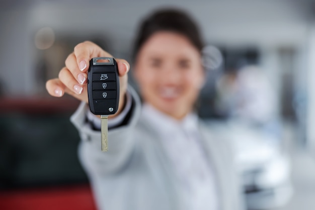 Close do vendedor de carros segurando e entregando as chaves de um carro em direção à câmera em pé no salão do carro.