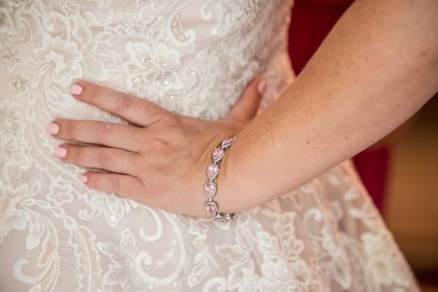 Close do vestido de noiva da noiva de lado, com a mão na cintura