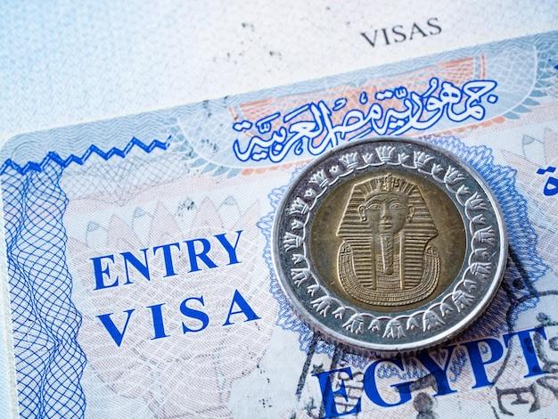Close do visto do egito em passaporte estrangeiro com retrato do faraó em moeda de libra egípcia