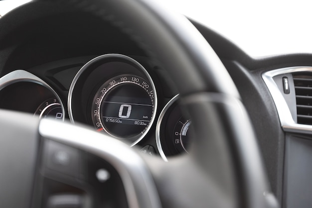 Close do volante e velocímetro dentro de um carro moderno