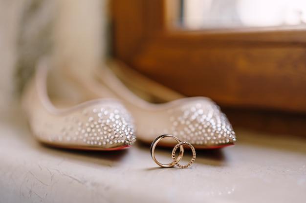 Close dos anéis de casamento e sapatilhas da noiva com miçangas