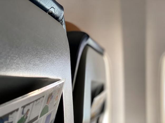 Close dos assentos da aeronave com instruções de segurança a bordo saindo do bolso traseiro. conceito de viagens e turismo.