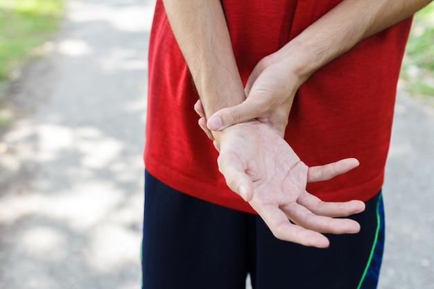 Close dos braços masculinos segurando o pulso dolorido dela devido ao exercício