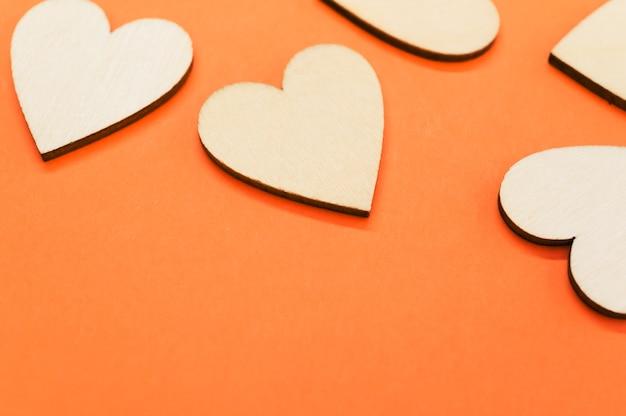 Close dos corações em forma de madeira na superfície laranja - espaço para texto