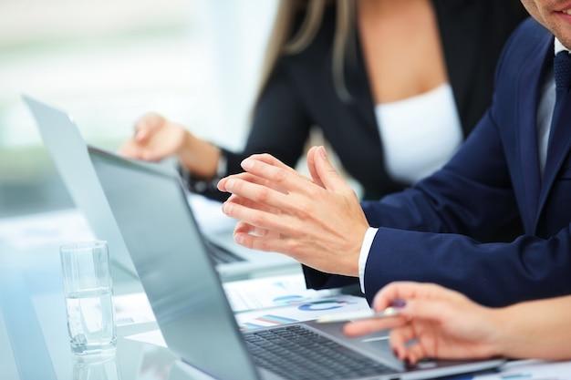 Close dos funcionários da empresa à mesa, trabalhando com o laptop no escritório