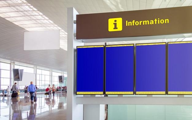 Close dos horários de voos do painel de informações vazio no aeroporto com passageiros desfocados andando em segundo plano