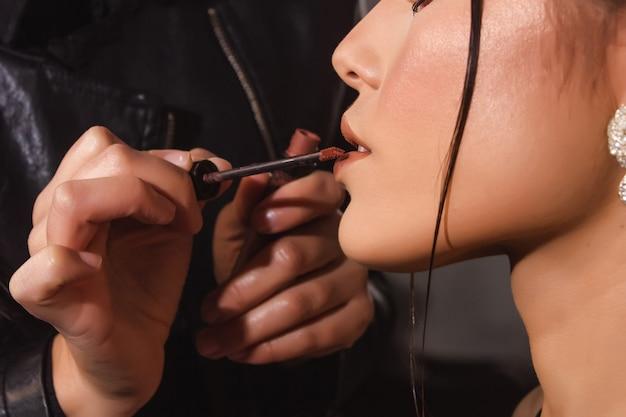 Close dos lábios de uma garota sexy sendo pintados por um maquiador.
