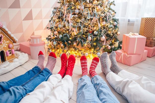Close dos pés da família em meias de lã perto da árvore de natal
