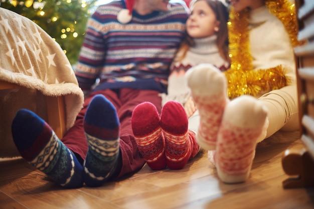 Close dos pés da família em meias de lã