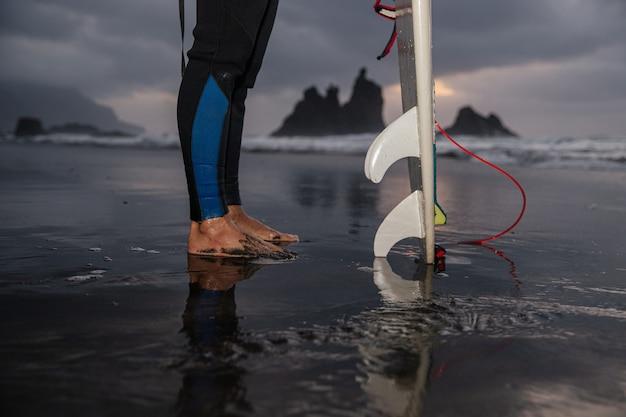 Close dos pés de um surfista vestindo roupa de neoprene e sua prancha de surf, ele está na praia durante o pôr do sol.