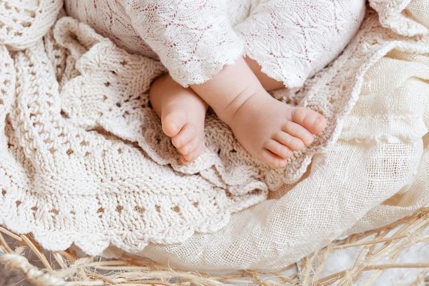 Close dos pés do bebê recém-nascido em xadrez de malha