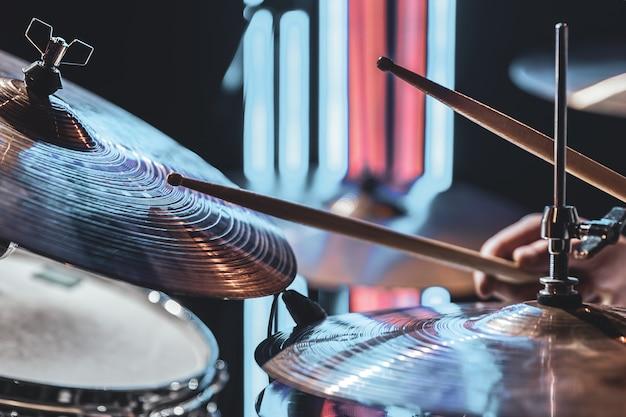 Close dos pratos da bateria enquanto o baterista toca com uma bela iluminação