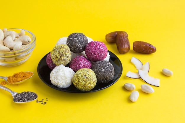 Close em diferentes bolas de energia na placa preta e ingredientes na superfície amarela