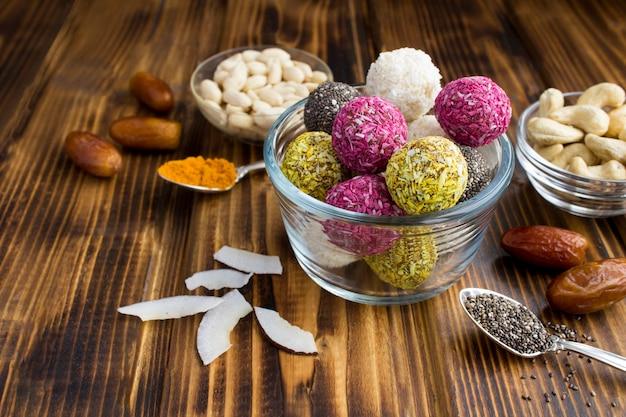 Close em diferentes bolas de energia na tigela de vidro e ingredientes na superfície de madeira