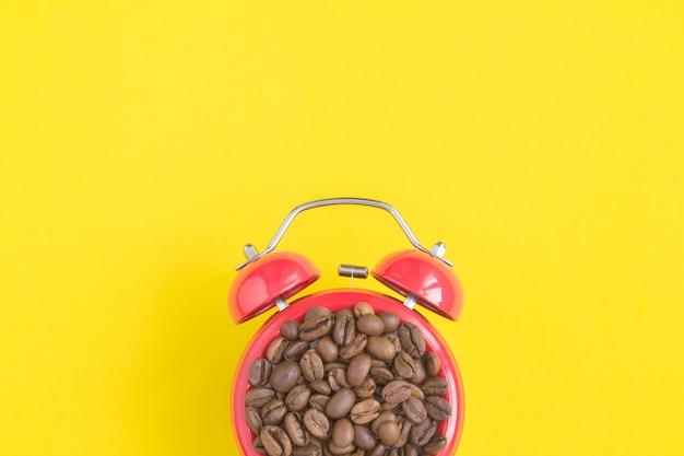 Close em grãos de café no mostrador do despertador vermelho sobre fundo amarelo