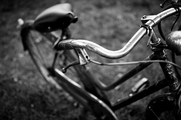 Close em tons de cinza de uma bicicleta velha com um fundo desfocado