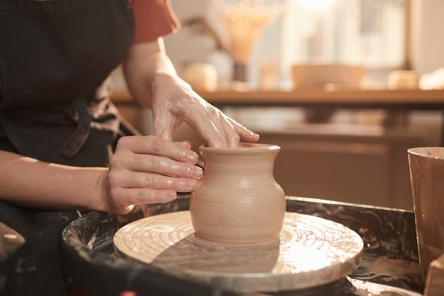 Close em tons quentes de mãos femininas moldando argila na roda de oleiro enquanto fazem cerâmica em uma oficina iluminada pelo sol, copie o espaço