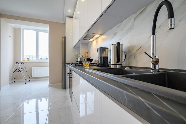 Close em um armário de cozinha moderno com chaleira elétrica, cafeteira e duas xícaras de chá de vidro