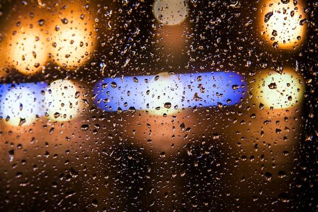 Close em um vidro de carro com um punhado de chuva e, no fundo, luzes de um brilho amarelo brilhante