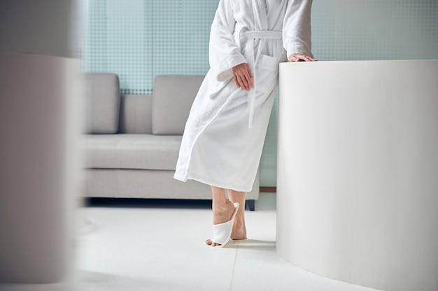 Close em uma senhora caucasiana de chinelos e roupão de banho em um centro de bem-estar